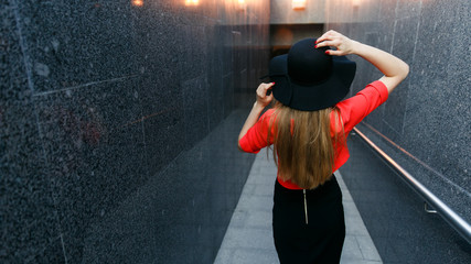 Photo from back of girl in black hat