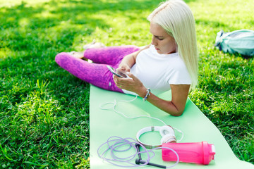 Photo of sporty woman with phone on rug