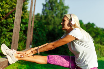 Image of sporty woman wearing headphones on stretching