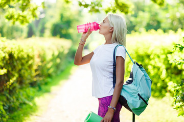 Photo of athletic girl drinking from bottle
