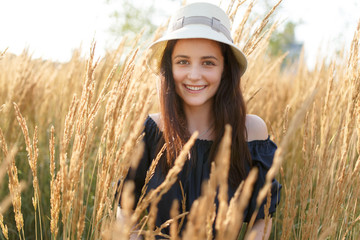 Picture of young woman in hat in wheat field