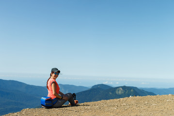 Photo of girl in sunglasses sitting on edge of hill