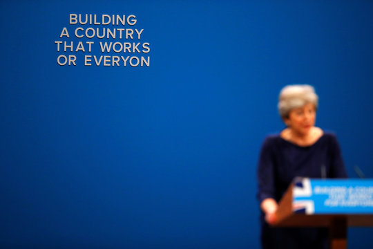 The wording on a slogan is changed after letters fell away from the backdrop as Britain's Prime Minister Theresa May addresses the Conservative Party conference in Manchester