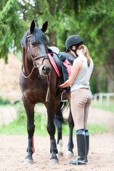 Young teenage girl owner harnessing chestnut stallion at stable place
