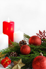 Christmas candle, spruce pine branches and Christmas decorations design in a New Year's style on a light background with copy space