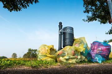 sacchetti di immondizia abbandonati vicino ad un prato