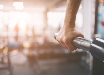 The hand is close-up. Workout in the gym. Dips on parallel bars . Indoor fitness.