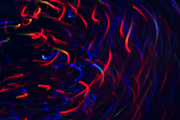 Abstract picture of colorful lines in motion on black background. Bokeh of defocused curves spinning into spiral, blurred neon blue and red leds, festive backdrop of city lights