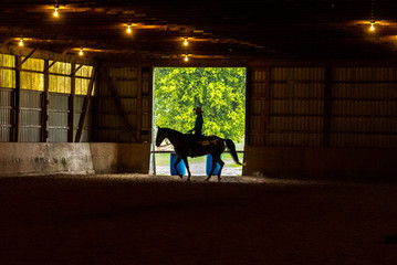silhouette of cowgirl riding horse inside large barn