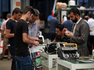 A man counts money using a cash counting machine at the Stock Exchange in Erbil