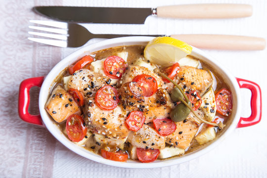 Salmon baked with sesame, tomatoes and zucchini. Close-up. Selective focus.