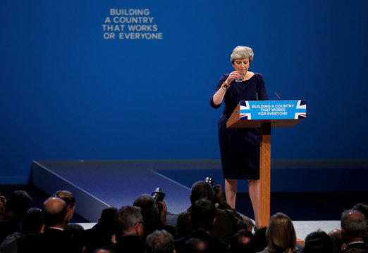The wording on a slogan is changed after a letter fell away from the backdrop as Britain's Prime Minister Theresa May addresses the Conservative Party conference in Manchester