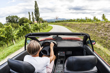 Young man driving with red vintage sports car through the vineyard on south styrian vine route. Windmill called Klapotetz in front.