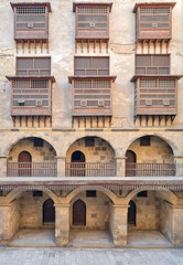 Facade of caravansary (Wikala) of Bazaraa, with vaulted arcades and windows covered by interleaved wooden grids (mashrabiyya), suited in Tombakshia street, Al Gamalia district, Medieval Cairo, Egypt