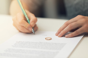 woman signing marriage divorce papers