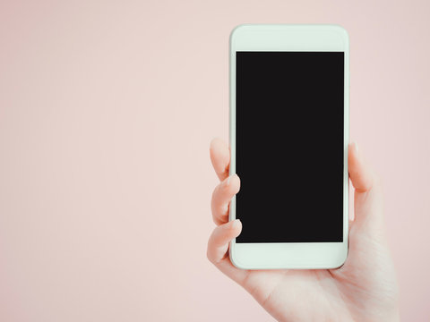 holding and show smart phone by asian woman beauty right hand with pink pastel background