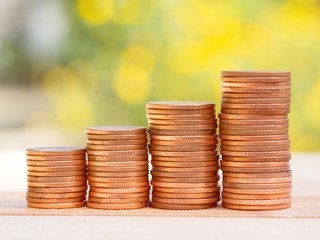 Four rows of rising growth golden stack coins with green nature background. Growing and saving money concept.