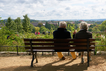 Älteres Rentner-Ehepaar sitzt auf einer Bank und genießt die Aussicht