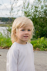 Portrait of a blond Slavic boy near river and the Urals village, Russia