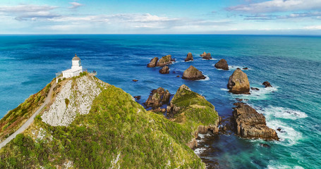 New Zealand aerial drone view of Nugget Point Lighthouse in Otago region and peninsula on South Island of New Zealand. Beautiful tourist destination and attraction seen from above.