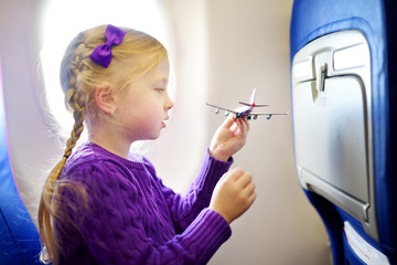 Adorable little girl traveling by an airplane. Child sitting by aircraft window and playing with toy plane. Traveling with kids.