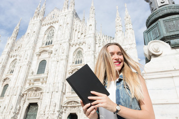 Pretty teenager tourist with her travel guide visiting the city. Copy space on the guide cover. Photo taken in Milan, Italy.