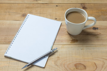 Open notebook with cup of coffee on wooden