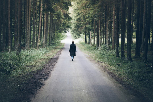 young blonde caucasian woman walking on narrow road through dark forest