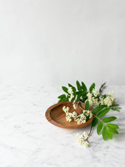 White blossoms on wooden plate