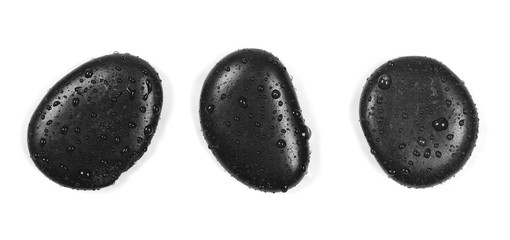 Black spa stones with water drops isolated on white background, top view
