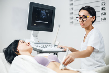 Doctor makes the patient women abdominal ultrasound. Ultrasound Scanner in the hands of a doctor. Diagnostics and sonography in clinic.
