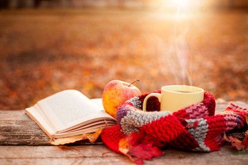 Open book with apple and yellow tea mug with warm scarf