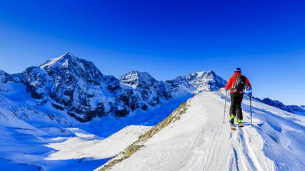 Mountain ski walking up along a snowy ridge with skis in the backpack. In background blue cloudy sky and shiny sun and Tre Cime, Drei Zinnen in South Tirol, Italy. Adventure winter extreme sport.