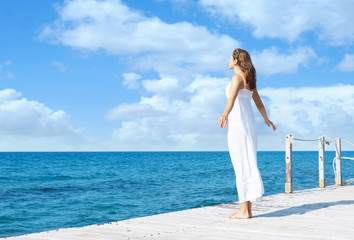 Back view of a young woman standing on a pier.  Sea and sky background. Vacation and traveling concept.