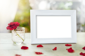 White frame and rose petals on table