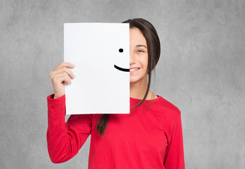 Teenager covering half of her face with a smiling emoticon