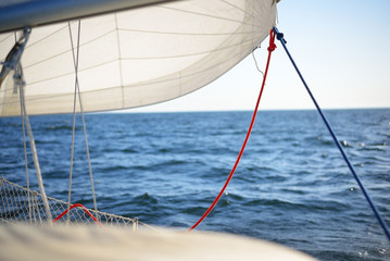 Close up view of a staysail and its sheets from the deck of a yacht in an open sea on a summer day