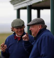 Competitors smoke cigars at the 18th hole during the World Hickory Open at Kilspindie Golf Course in Aberlady