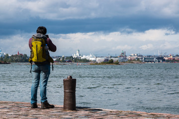 The man photographer stands on the edge of the pier in the fortress of Suomenlinna and takes pictures of the port of Helsinki Finland.