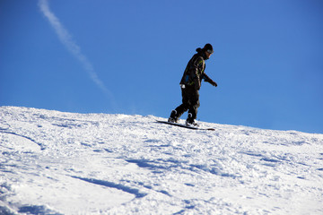 Small snowboarder on blue sky backdrop.