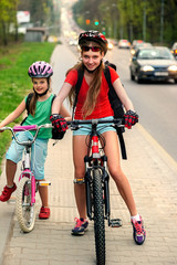 Bikes bicyclist girl. Girls wearing bicycle helmet with rucksack ciclyng bicycle. Bike share program save money and time at city street. Children travel unaccompanied.