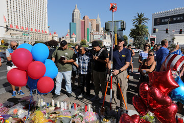 A member of the FBI Evidence Response Team works to map the crime scene near a memorial in the middle of Las Vegas Boulevard following the mass shooting in Las Vegas