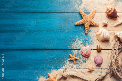 Wall mural beach scene concept with sea shells and starfish on a blue wooden background