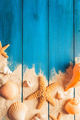 Fototapete - beach scene concept with sea shells and starfish on a blue wooden background