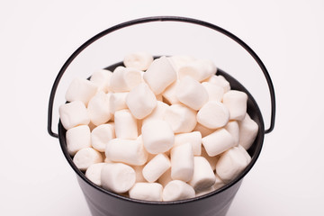 White mini marshmallows background close-up texture. A pile of mini white puffy marshmallows in black bowl isolated on white background. Wallpaper for desktop. Food background