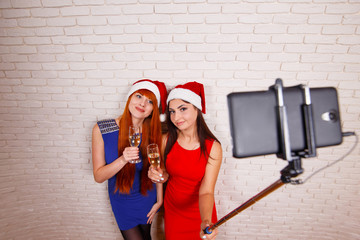 Two beautiful women in Santa caps having fun, drinking champagne, taking self portrait with a smartphone and selfie stick. New Year, Christmas, celebration, party, technology concept