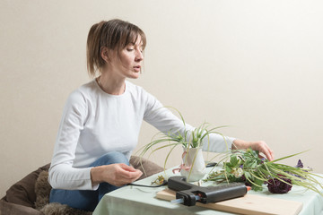 Mature adult woman making flower decoration at home
