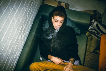 Addicted young man consuming illegal drugs by oral administration while lying down on the sofa in a dirty room at home