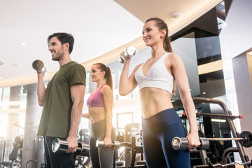 Low-angle view of three young people smiling while alternating dumbbell bicep curl exercise during group workout at the gym