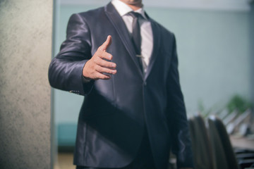 closeup of a businessman holds out his hand to say Hello and help
